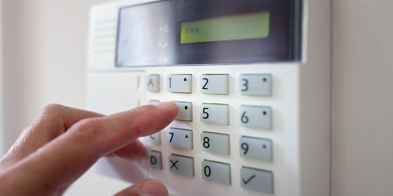 kobieta ustawia alarm domowy chroniący mieszkanie przed złodziejami